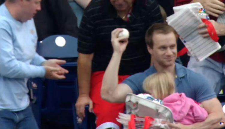 Pai pega a bola de basebol segurando a filha e cachorros quentes.